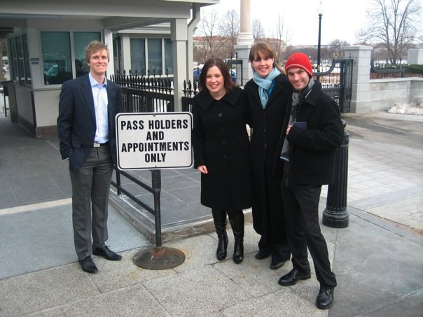 "Photo of four people with a sign that says ""Pass holders and appointments only"""
